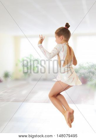 Beautiful little girl gymnast dressed in sports swimsuit, jumps high.On the background of the school hall with large Windows.