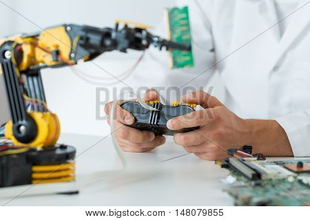 Cropped picture of a scientist controlling a robot with a joystick