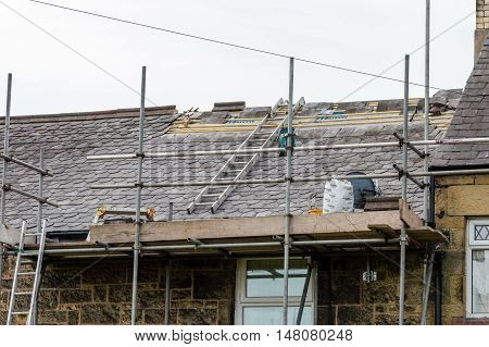 WREXHAM WALES UNITED KINGDOM - AUGUST 11 2016: Restoration of decorative slate roof on a residential terraced house in North Wales.
