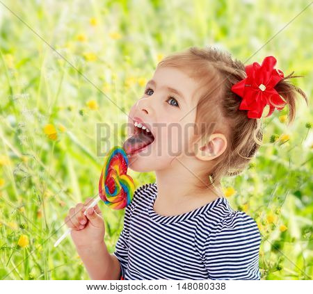 Cute little blonde girl with a red bow on her head, with pleasure licking colorful candy on a stick. Visible language which was painted in a candy color. Close-up.On blurred background of green grass