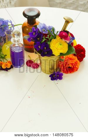 Fresh flowers, mortar and bottles of potions, herbal medicine concept, copy space on white wooden table