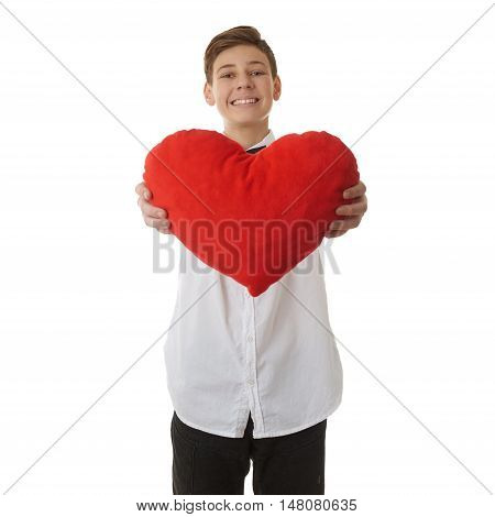 Cute teenager boy in white shirt holding with red plush heart over white isolated background, half body