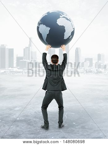 Back view of young businessman holding terrestrial globe on abstract city background. 3D Rendering. International business concept