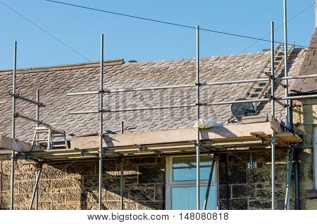 WREXHAM WALES UNITED KINGDOM - AUGUST 12 2016: Restoration of decorative slate roof on a residential terraced house in North Wales.