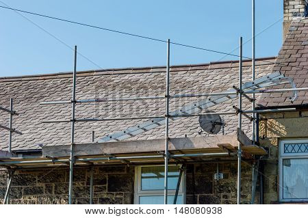 WREXHAM WALES UNITED KINGDOM - AUGUST 15 2016: Restoration of decorative slate roof on a residential terraced house in North Wales.