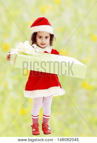 Cute little girl in a coat and hat of Santa Claus, holding a big green box , tied with a bow.Bright, floral yellow-green blurred background.