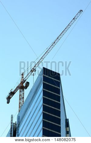 Crane and high-rise modern building under construction.