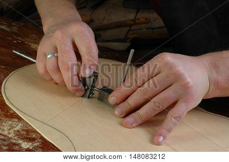 Luthier makes installation rosette classical guitar with the help of circular knives and gouges