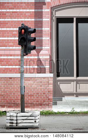 Street scene. Traffic light behind a temporary brick wall painted canvas
