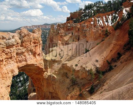 View Brice Canyon, National Park in Utah in the US, with a natural arch. Photo taken in late spring: there is still snow at the foot of trees. Light, natural colors.