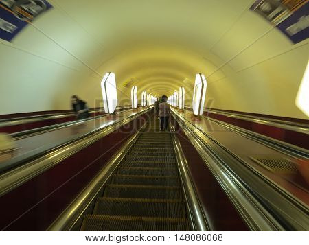The descent into the underground on the escalator with people