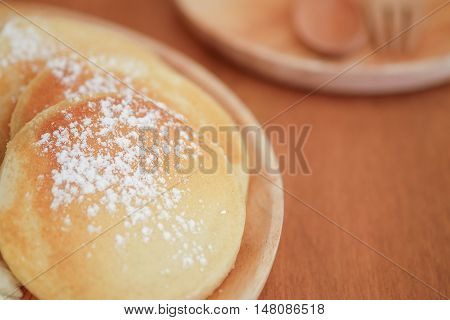 Pancakes with icing sugar on wood plate. Sweet dessert. with selective focus