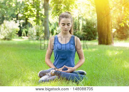 meditating teenage girl in a park in summer