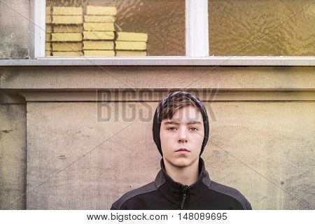 serious teenage boy with cap and books