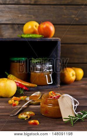 Chutney of apples and hot peppers on a dark background. Selective focus.