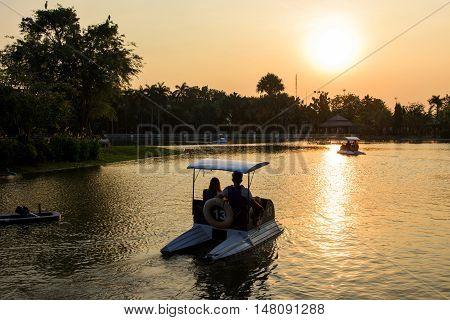 Couble In Pedal Boat At Sunset
