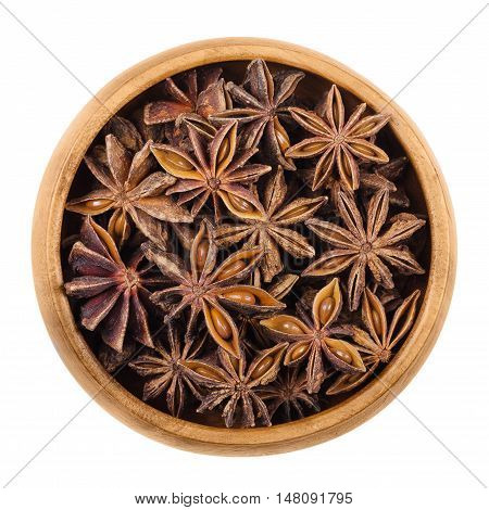 Star anise seeds in a wooden bowl over white. Dried fruits of Illicium verum, also Chinese star anise or badiam. Closely resembles anise in flavor. Used for baking, sambuca, pastis and absinthe.