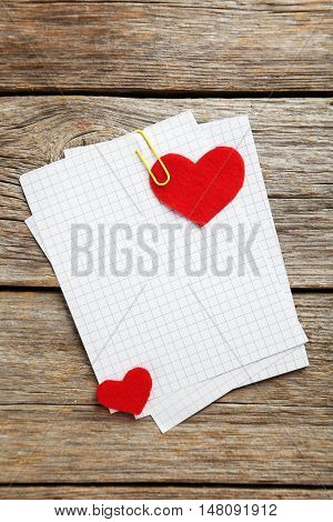Red hearts and sheet of blank paper on a grey wooden table