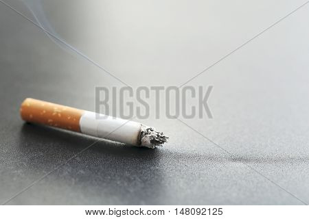 Cigarette with ash on a black background