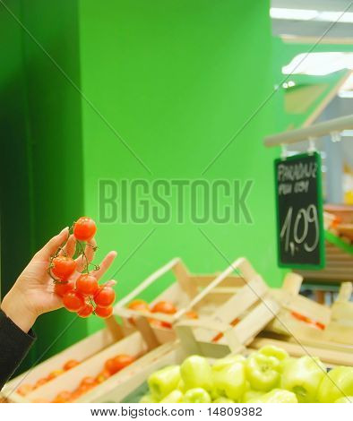 woman holding tomato in super market