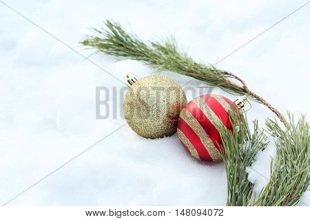 Christmas baubles with fir-tree branch on the white snow