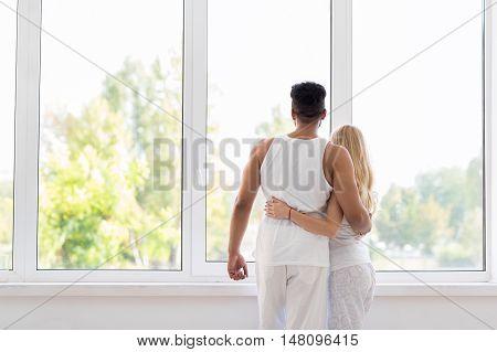 Young Beautiful Couple Stand Near Big Window Embrace, Happy Smile Hispanic Man And Woman Lovers Hug Back Rear View