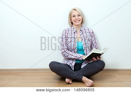 Beautiful middle aged woman at home sitting on the floor relaxing in her living room reading book.