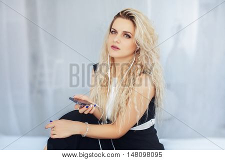 A young woman listening to music through headphones on the bed. The concept of beauty and lifestyle.