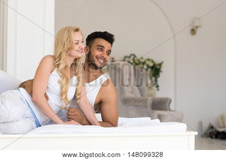 Young Couple Lying In Bed Looking At Each Other, Happy Smile Hispanic Man And Woman Lovers In Bedroom