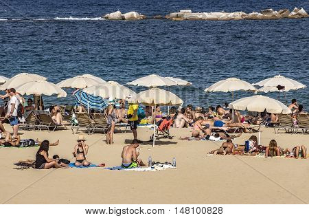 BARCELONA SPAIN - JULY 4 2016: A crowd of bathers in La Barceloneta Beach in Barcelona Spain. This popular beach hosts about 500000 visitors from everywhere during the summer season.