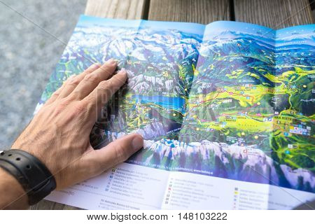RIBCEV LAZ SLOVENIA - AUGUST 25 2016: Unidentifiable man looking at map of Bohinj lake area located in Slovenia national park Triglav.