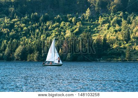RIBCEV LAZ SLOVENIA - AUGUST 24 2016: Unidentifiable men sailing at Bohinj lake located in Slovenian national park Triglav famous location for various outdoor sport activities.