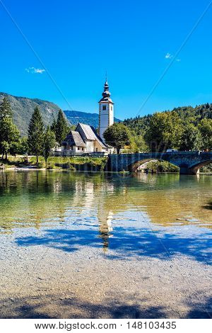 BOHINJ LAKE SLOVENIA - AUGUST 24 2016: Church of St. John the Baptist at Bohinj Lake is over 700 years old and is a beautiful example of Middle Age architecture and fresco painting in Slovenia.