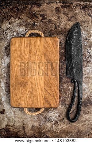 Wooden chopping board and old knife on rustic table