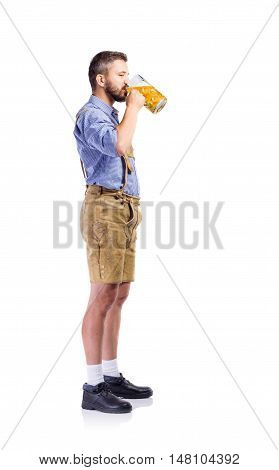 Handsome hipster young man in traditional bavarian clothes holding a mug of beer, driking from it. Oktoberfest. Studio shot on white background, isolated.