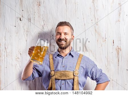 Handsome young man in traditional bavarian clothes holding a mug of beer. Oktoberfest. Studio shot on white wooden background.