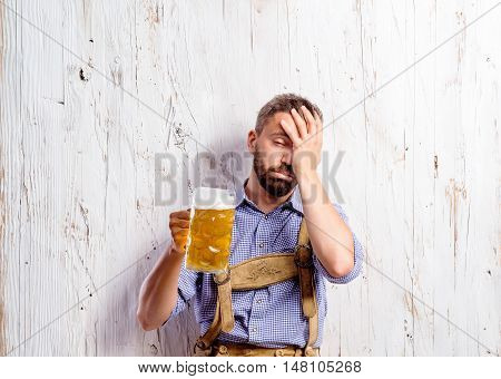 Exhausted drunk young man in traditional bavarian clothes holding a mug of beer suffering hangover and headache. Oktoberfest. Studio shot on white wooden background.