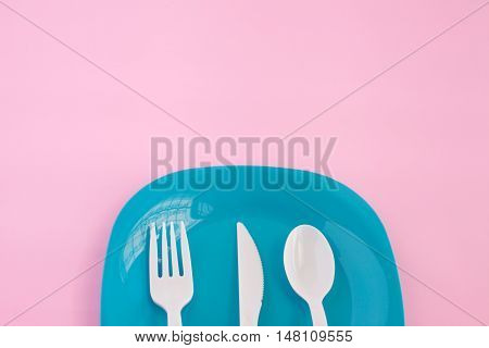 fork ,knife and spoon put on colorful plastic plate with pink background