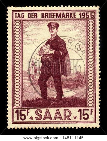 Germany, Saarland - CIRCA 1955: a stamp printed in the Saar, Germany shows postman and church of Illingen, circa 1955