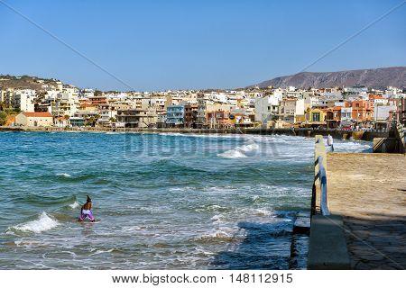 CHANIA, CRETE, GREECE - JULY 2016: Young boy is swimming at coastline of mediterranean sea near Chania town on Crete island, Greece