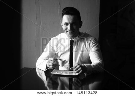Man young handsome elegant model wears shirt skinny necktie sits at table holds cup of coffee and smiles in camera indoor black and white on grey background
