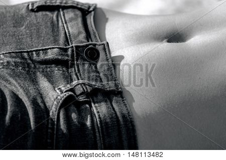 the female part of the body, stomach, navel, wear your favorite jeans, skinny, slim, black and white photo,  the girl lies,