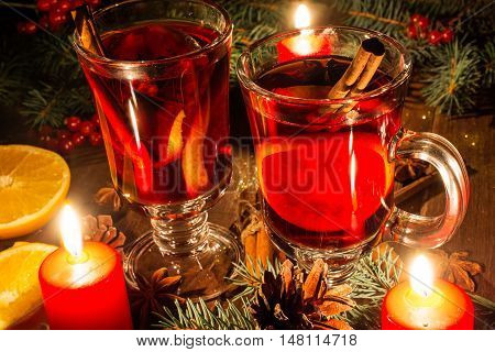 christmas mulled wine with spices and orange in the candle light. festive romantic drinks background