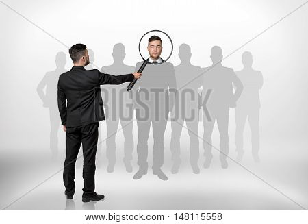 Back view of a businessman looking through magnifying glass on the head of the man that is surrounded by grey silhouettes. Hiring and giving a job. Employment and occupation.