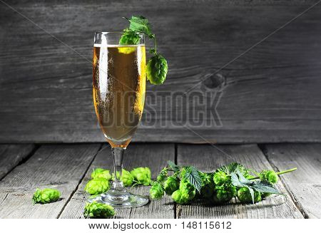 Glass of cold beer and green hops on a wooden table