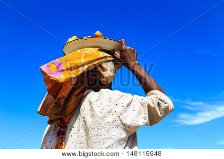 Woman Carrying A Dish With Food On Her Head Seen From Behind