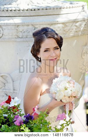 Beauty Bride In Bridal Gown With Bouquet And Lace Veil In The Nature. Beautiful Model Girl In A Whit