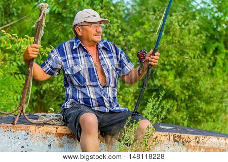 a dreaming  fisherman with a fishing rod is sitting by the river on a gorgeous sunny day in the background of green trees