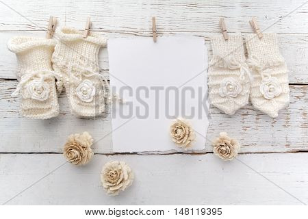 Baby New Born or baptism Greeting Card. Blank card with baby girl shoes and gloves on white wooden background.