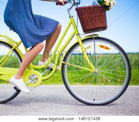 Side View Of Woman Riding Retro Bicycle In Countryside